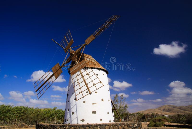 View on  ancient white windmill with brown wings against blue sky with few scattered clouds - Fuerteventura, El Cotillo stock photo