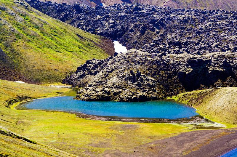 View on  blue crater lake with volcanic lava ash after eruption with green valley. Kerið, Kerio, Kerid, Kerith Iceland royalty free stock images