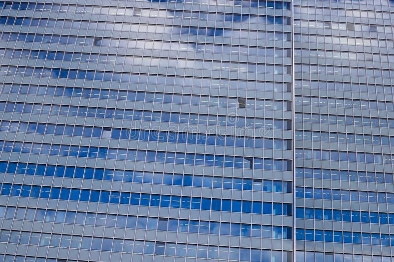 View on isolated glass facade of skyscraper with countless windows and reflection of clouds and sky - Düsseldorf, Germany. View on isolated glass facade of royalty free stock image