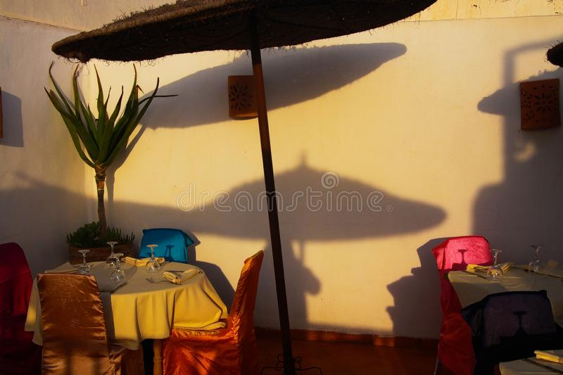View on isolated terrace of riad  medina of arabic town with table, chairs and reed umbrellas throwing shadows on wall royalty free stock images