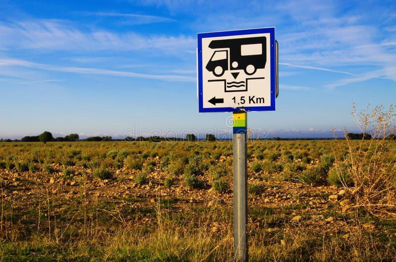 View on isolated white direction sign with camper against blue sky and lavender field. Sign gives information for next cesspool. For feces disposal. Provence royalty free stock images