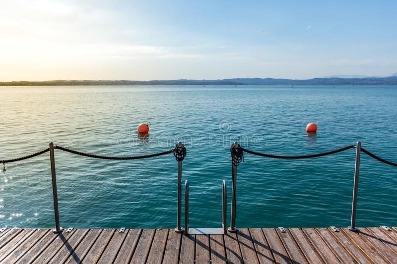 Wooden jetty on peacefull Garda Lake, Sirmione. Italy stock photography