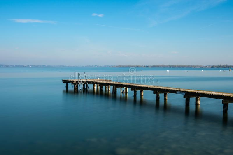 Wooden jetty on peacefull Garda Lake, Sirmione. Italy royalty free stock images