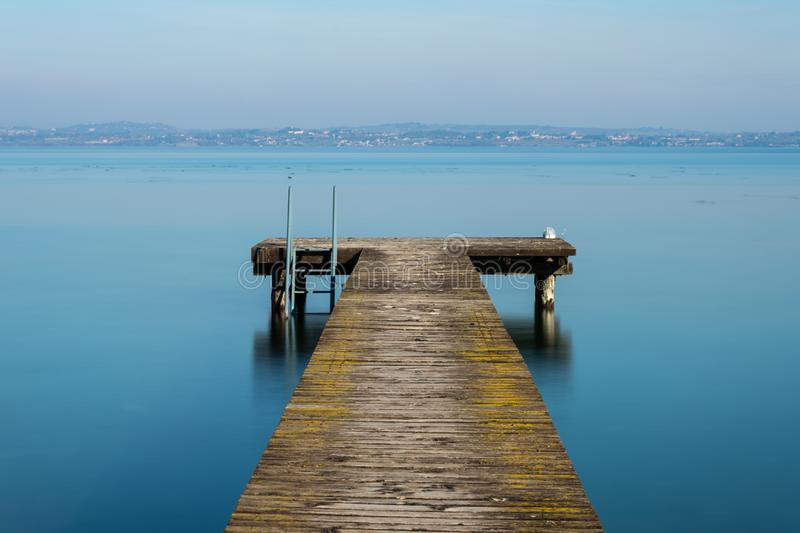 Wooden jetty on peacefull Garda Lake, Sirmione. Italy stock images