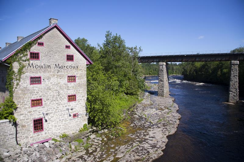 View of the Jacques-Cartier River and 1872 patrimonial Marcoux Mill during sunny summer morning. Pont-Rouge, Quebec, Canada royalty free stock photos