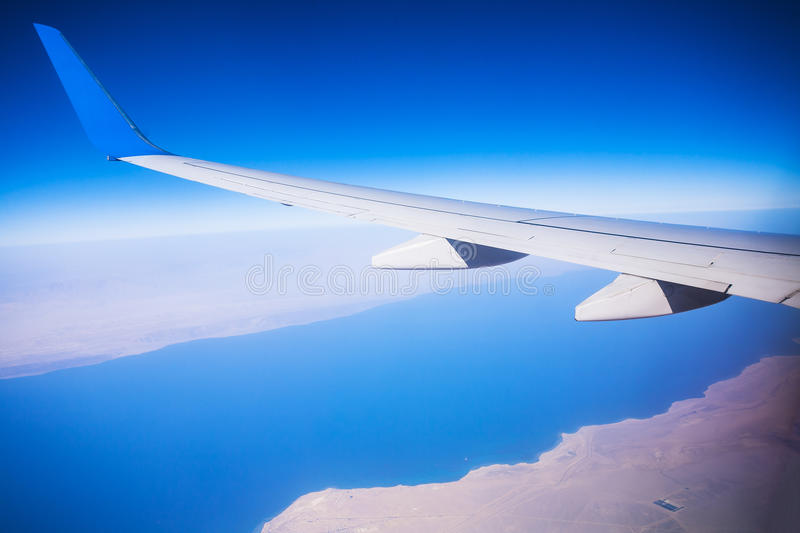 View of jet plane wing with blue sky royalty free stock photography