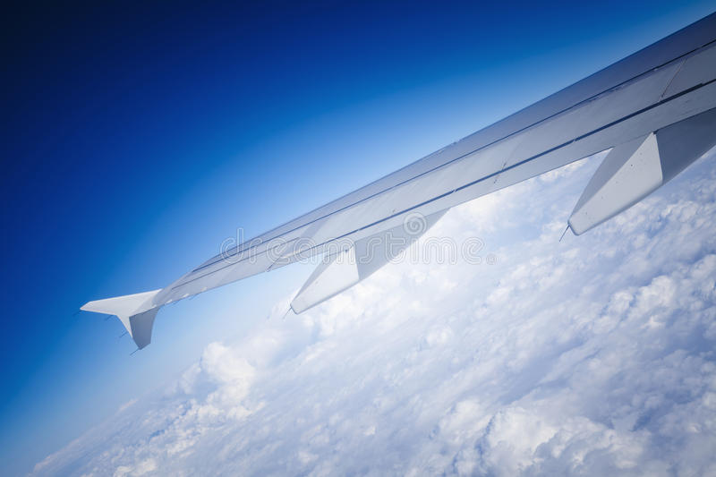 View of jet plane wing with cloud patterns royalty free stock photo