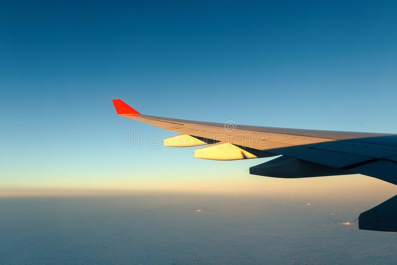 View of jet plane wing with cloud patterns stock images