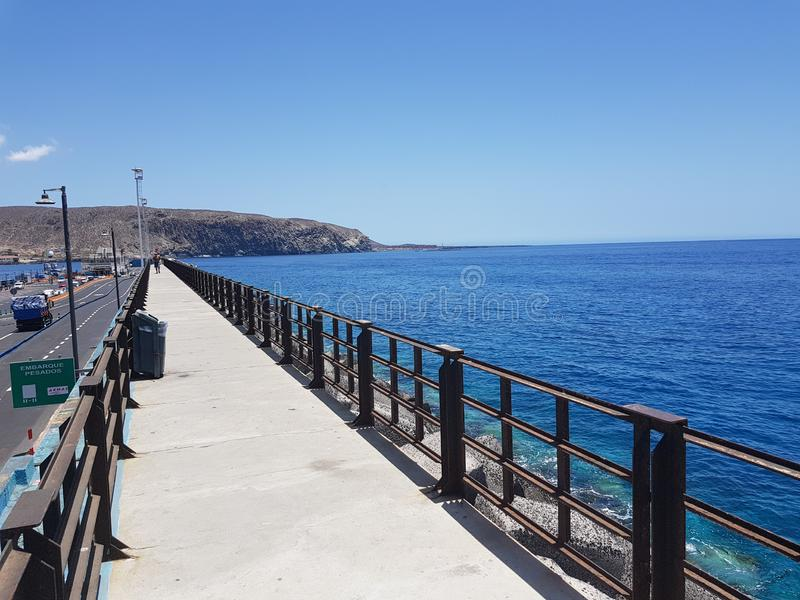 View of Jetty and concrete shore line in Las Cristiano`s Tenerife on a hot summer day. With blue sky and ocean sea royalty free stock image