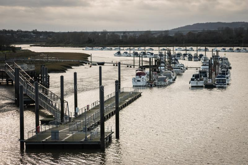 View of a jetty and pier leading to a flotilla of moored yachts on the River Medway in Rochester, England, UK stock photo