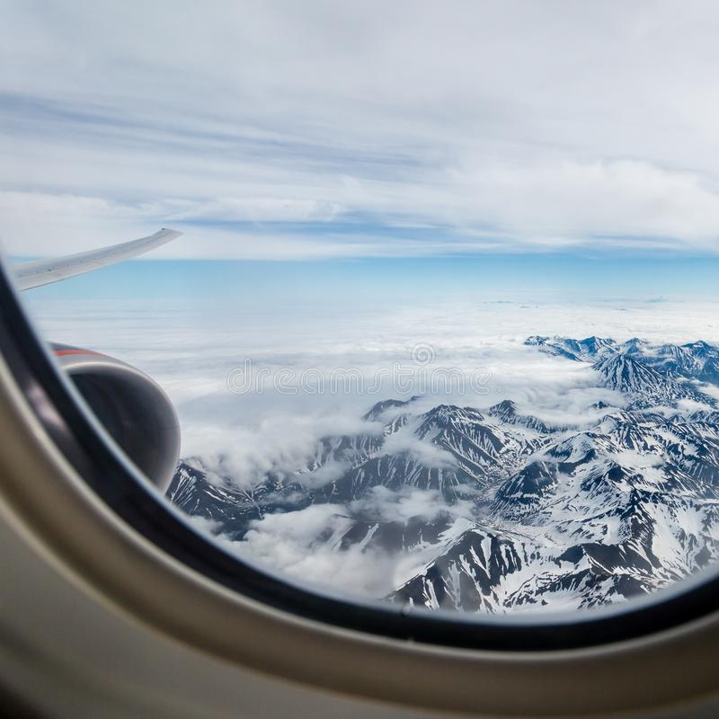 View of the Kamchatka mountains from the airplane porthole. Mountain landscape royalty free stock images