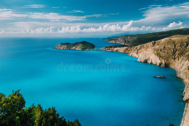 View of Kefalonia west coastline. Assos village town and Frourio peninsular. Beautiful milky blue bay with brown rocky royalty free stock image