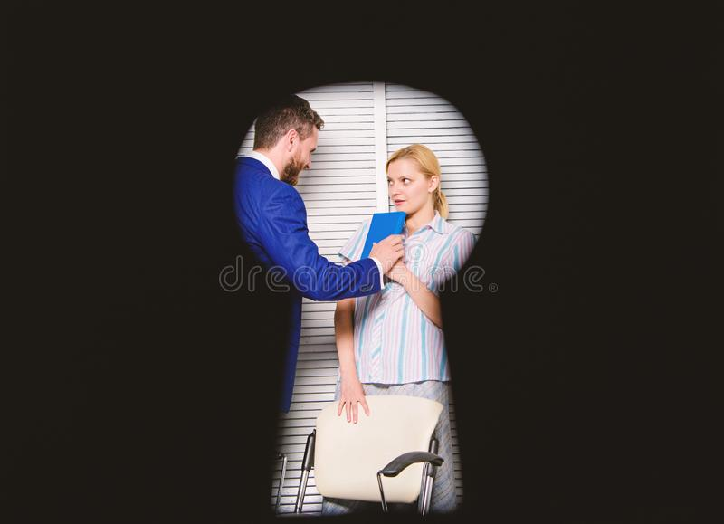 View through keyhole. Boss aggressive threatening violence. Witness of office crime. Woman suffer violence in office. Dirty secret and blackmail stock image