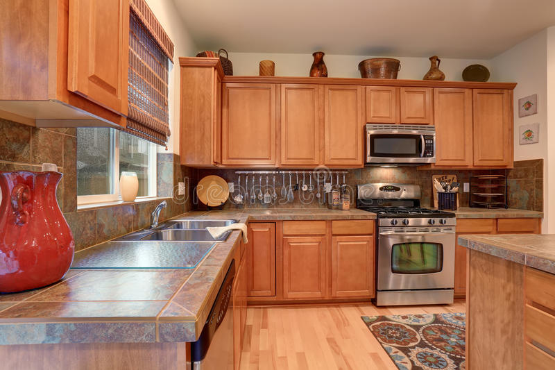 View of kitchen with hardwood storage combination, steel appliances . View of kitchen with hardwood storage combination, steel appliances and tile counter tops stock photos