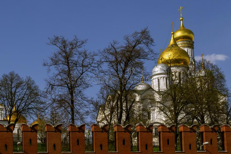 View on the Kremlin wall and and the white stone orthodox church with the bell tower of Ivan the Great. Moscow, Russia. stock photo
