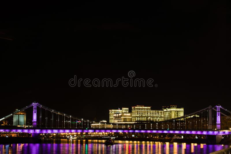 View on the The Krymskiy bridge in Moscow Russia in the evening or night with the embankment and light reflection in the river. View on the The Krymskiy bridge stock photo
