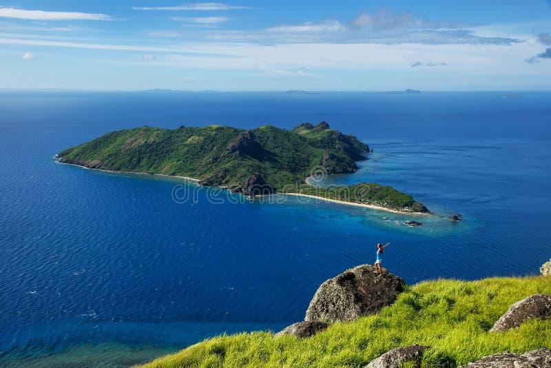 View of Kuata Island from Wayaseva Island with a hiker standing on a rock, Yasawas, Fiji royalty free stock photo