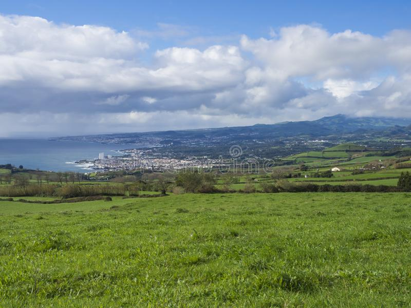 View on Lagoa city ocean bay with lush green grass hills, fields and pastures, blue sky and white clouds. Sao Miguel stock photography