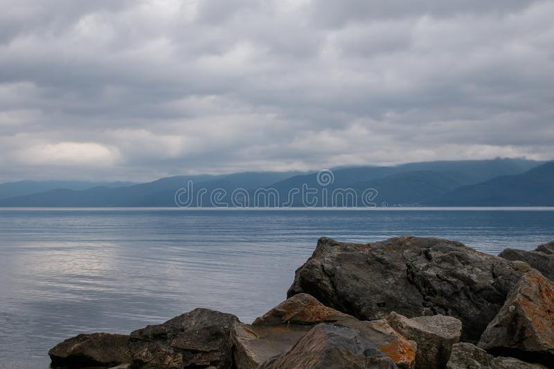 View of Lake Baikal in cloudy weather. Near the village of Kultuk, Irkutsk Region, Russia. In the foreground are large stones royalty free stock photos