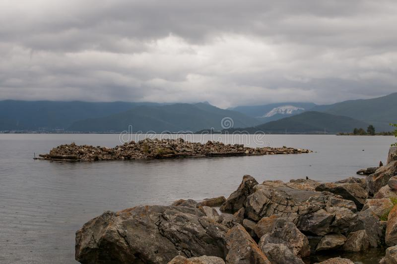 View of Lake Baikal in cloudy weather. Near the village of Kultuk, Irkutsk Region, Russia. In the foreground are large stones stock image