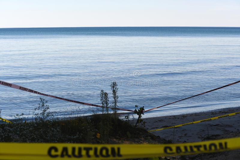 View of lake with yellow caution tape and danger signs overlooking the shoreline stock photography