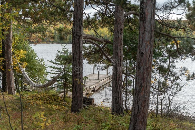 View of a lake dock through the pine trees of a forest. Wonderful travel destination is fishing from the lake docks in the Upper Peninsula of Michigan in the stock photography