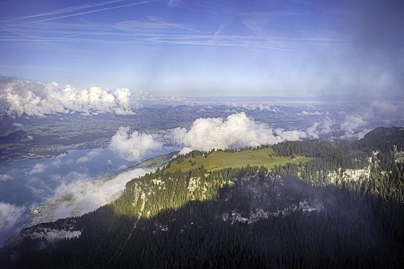 View of Lake Thun and Bernese Alps including Jungfrau, Eiger and Monch peaks from the top of Niederhorn in summer stock photography