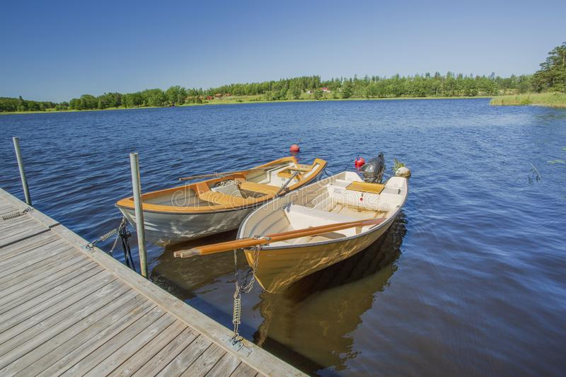 View of lake with two boats parked in shore on blue sky background. royalty free stock photo