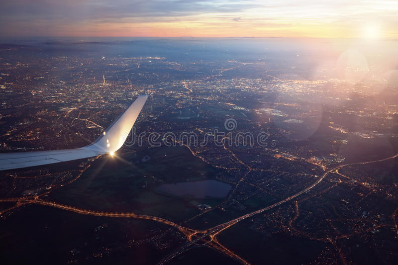 View from landing airplane window of city at sunset royalty free stock photography