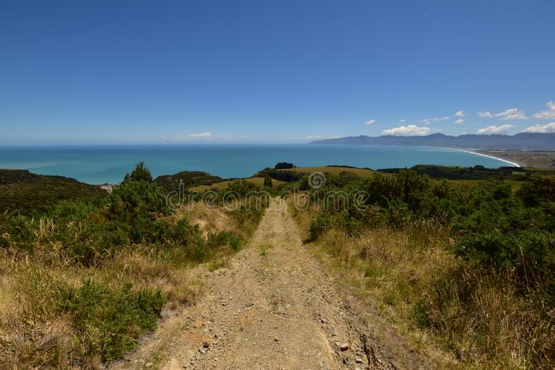 Cape Palliser bay view with gravel track in the front royalty free stock photo