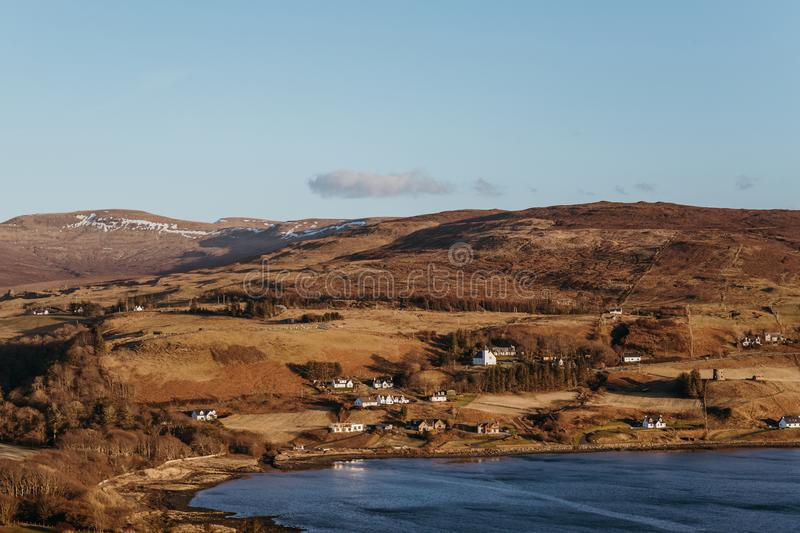 View of landscape and a small coastal village on Isle of Skye, Scotland. View of landscape and a small coastal village on Isle of Skye, Scotland, during golden royalty free stock images