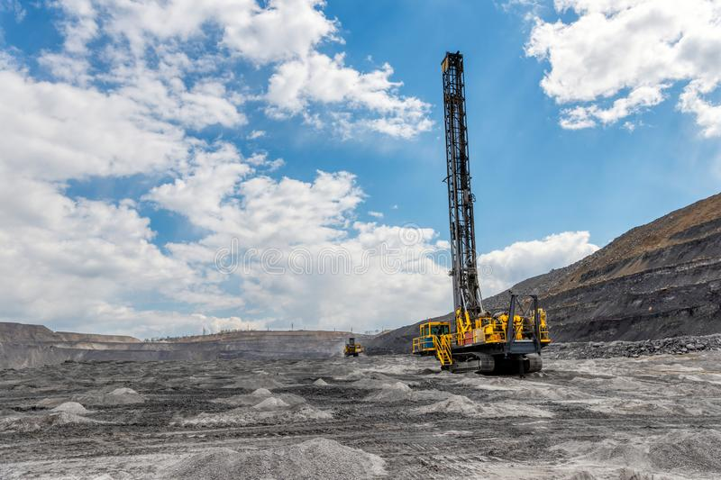 View of a large quarry for the extraction of limestone and coal. The drilling rig makes wells for laying emulsion royalty free stock images