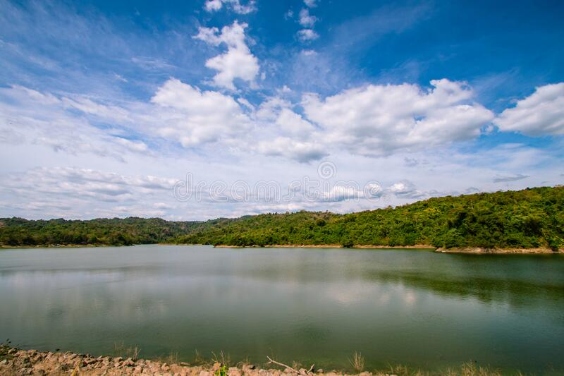 View of a large reservoir with mountains behind under the blue sky. stock image