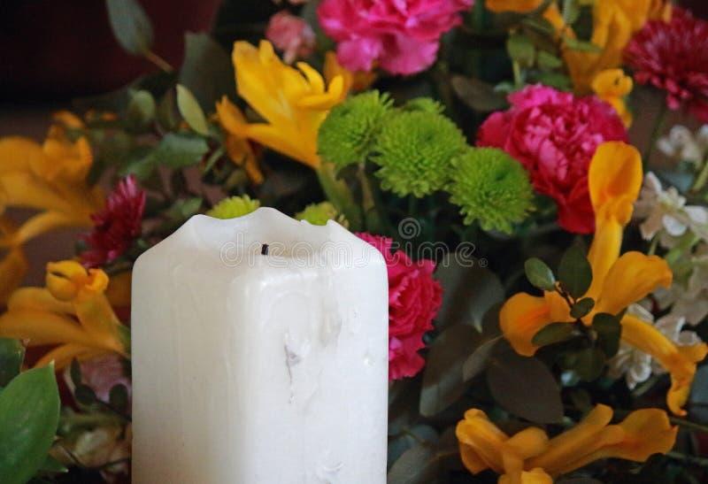 LARGE WHITE CANDLE & FLOWERS royalty free stock photo