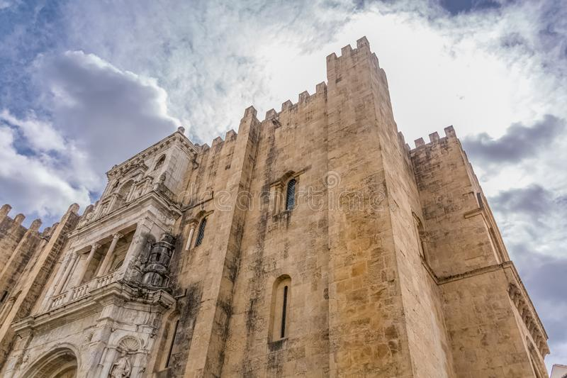View of lateral facade of the gothic building of Coimbra Cathedral, Coimbra city and sky as background, Portugal. Coimbra / Portugal - 04 04 2019 : View of royalty free stock image