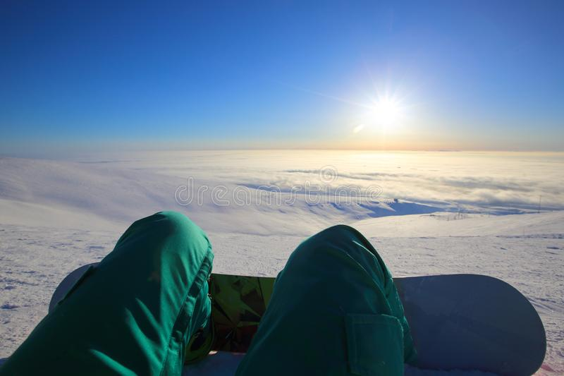 Snowboarder sitting high in mountains stock photography