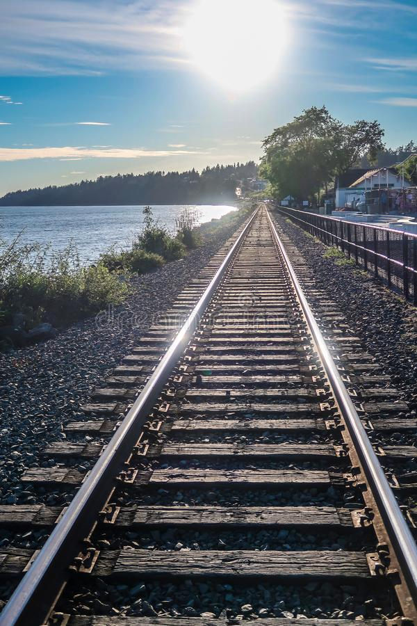 View of the length of railway track with glorious sunlight rays, river, distant mountains and greenery creating scenic landscape, stock photo