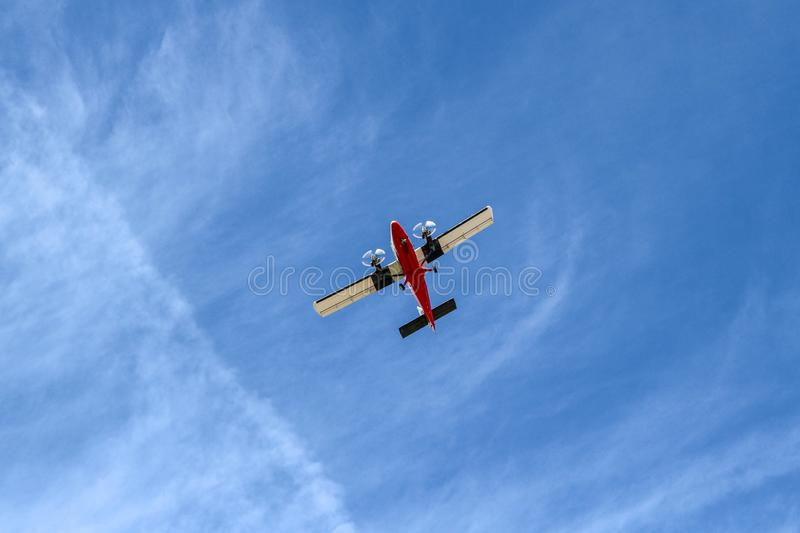 Small Airplane Flying at Low Altitude Under Blue Sky Viewed from Below. View of a light aircraft flying at low altitude under a blue sky viewed from below. Photo royalty free stock image