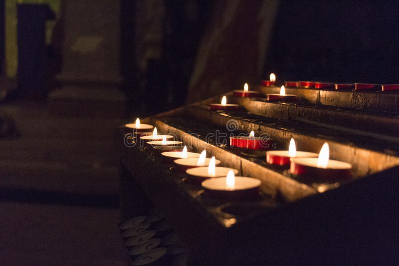 The view of lighted tealight candles. Burning candles. The view of lighted tealight candles in church stock photo