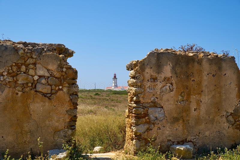 The view of the lighthouse through a break in the old wall. Sesimbra, Portugal royalty free stock images