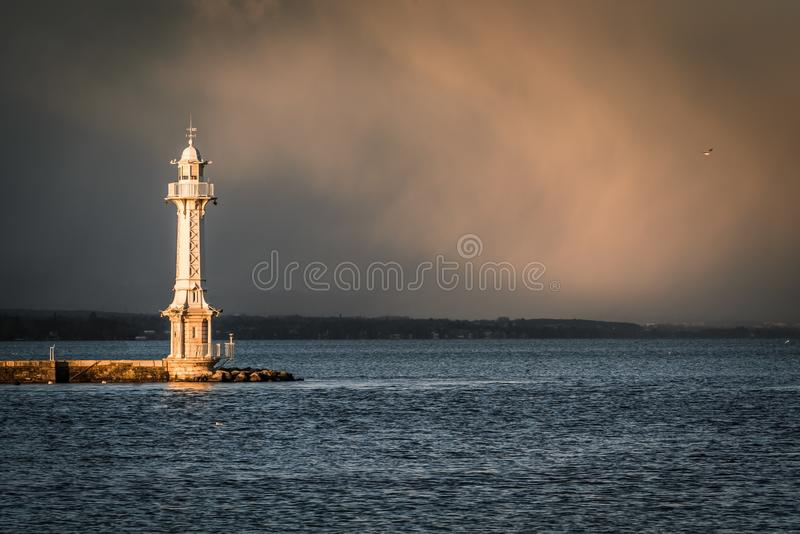 View of lighthouse on Lake Geneva with storm clouds in background. stock photo