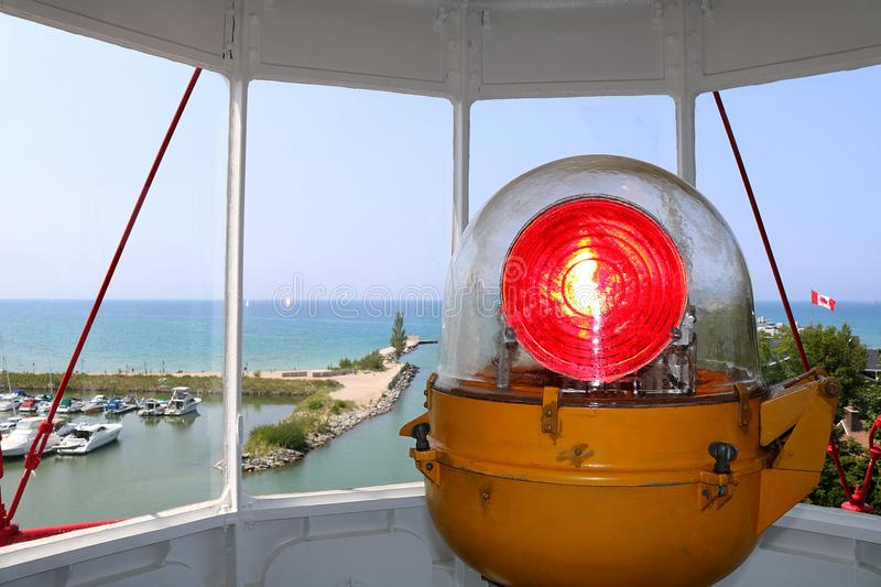 Close up of Lighthouse Lamp. View of lighthouse light bulb with red lens from inside the top of the lighthouse looking out over marina and boats on Lake Huron royalty free stock photography