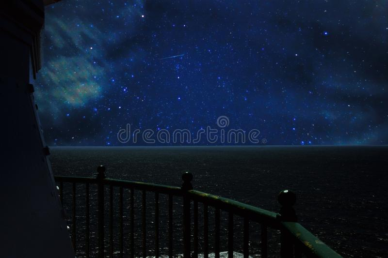 View from lighthouse to the ocean on a starry night royalty free stock photography