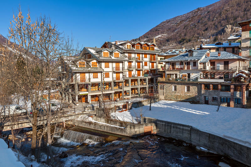View of Limone Piemonte. Stream and houses in town of Limone Piemonte covered with snow - popular alpine winter resort in Italy royalty free stock photography