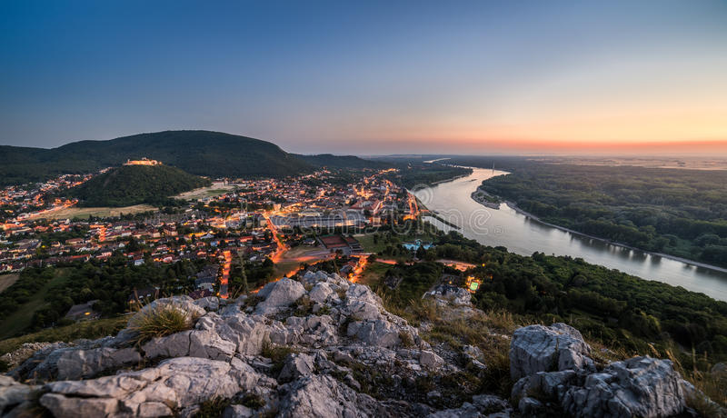View of Lit Small City with River from the Hill at Sunset royalty free stock image