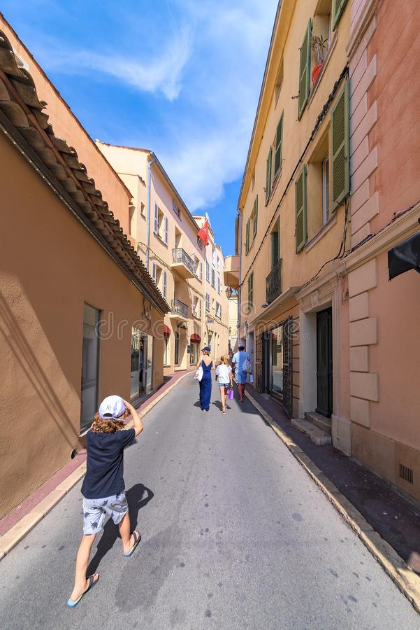 View of a little boy in a narrow French street, chasing his parents who are on holiday in France royalty free stock images