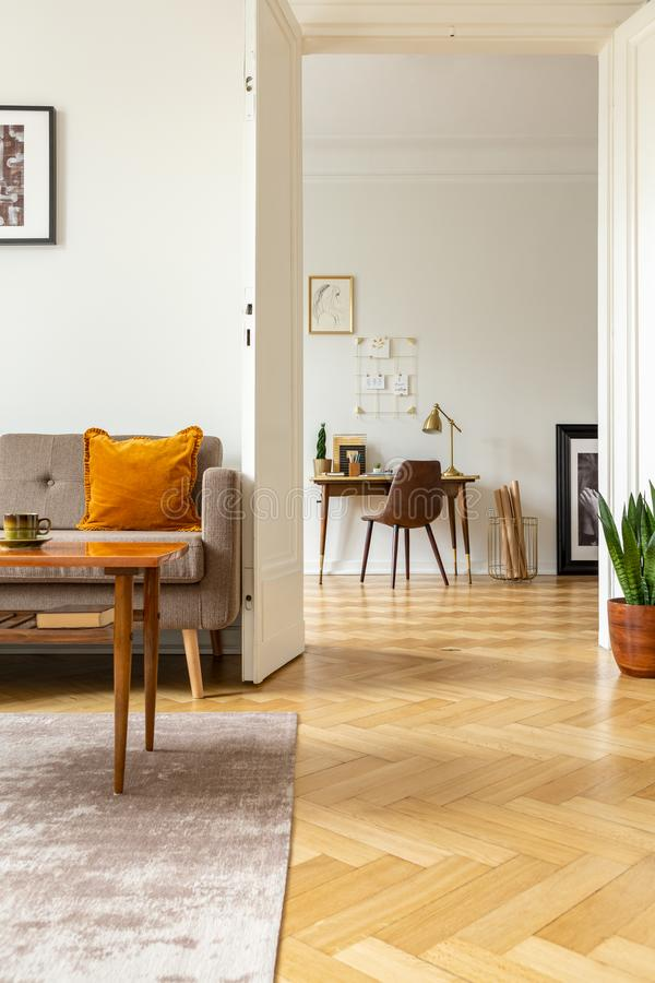 View from the living room with herringbone parquet floor into a home office interior with golden organizer above a wooden desk royalty free stock image