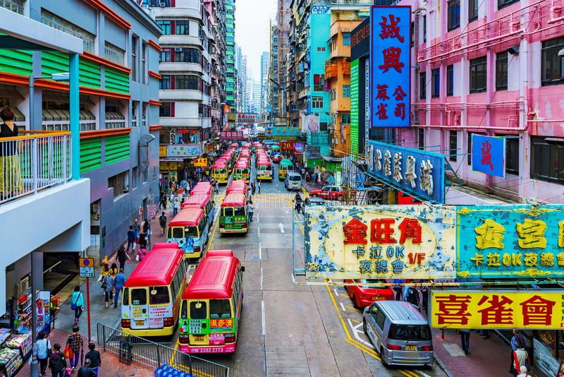 View of a local bus station and street. HONG KONG, CHINA - APRIL 24: This is a view of a local bus station in Mongkok on a busy street with signs and typical royalty free stock photos