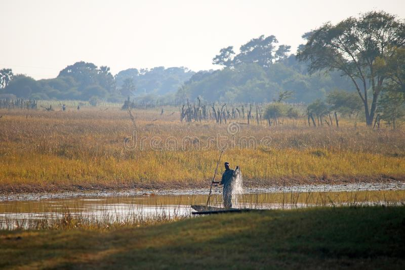 LOCAL FISHERMAN CASTING NETS FROM A SMALL BOAT IN A RIVER IN AFRICA stock photo