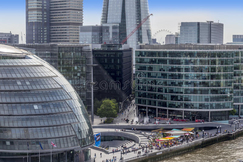 View of London City Hall from Tower Bridge. Showing the sunken amphitheatre called The Scoop, the base of the shard and the millennium Wheel royalty free stock photography